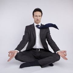 young businessman meditating in yoga lotus pose on white backgro