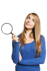 Pensive young female holding magnifying glass