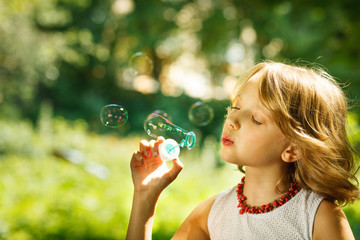 Funny little girl blowing soap bubbles outdoor