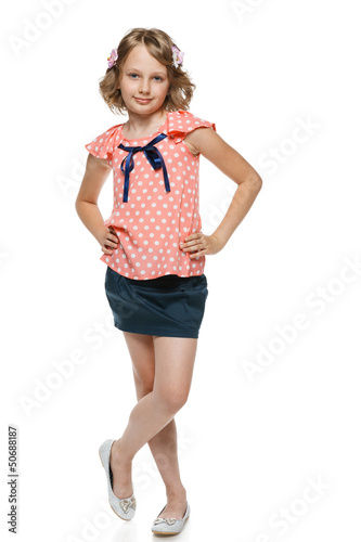 Little girl standing wiht hands on hips in full lenght