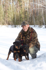 The man holds on a lead of two hunting dogs Jagdterriers in the