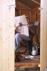 Man reading in garden shed