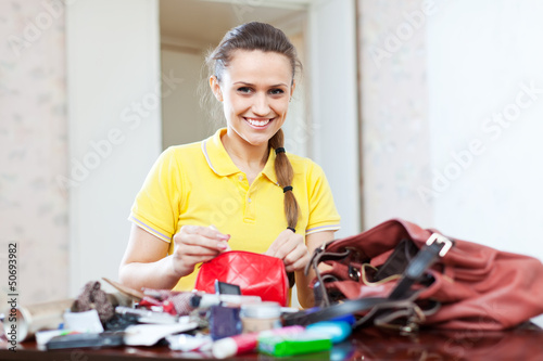 Smiling girl looking for something in purse