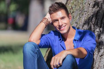 man sits next to tree & smiles