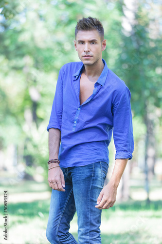serious young man poses in park