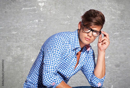 Fashion young man holding his glasses