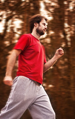 Forty years old man during a running workout in autumn forest
