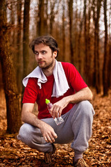 Runner man having a rest after jogging in autumn forest