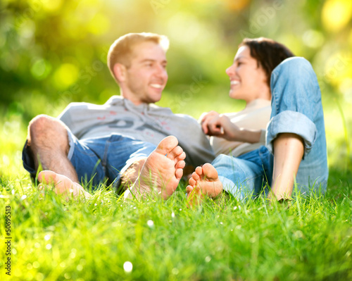 Park. Young Couple Lying on Grass Outdoor