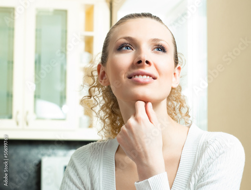 Young smiling blond woman thinking