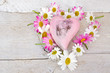 Romantische Dekoration: Holzherz mit Gänseblümchen