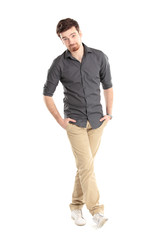 stylish young man standing with hands in pockets
