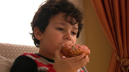 Little boy likes donut