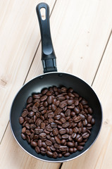 Frying pan with roasted coffee beans, view from above