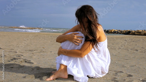 Sad lonely woman sitting on the beach thinking