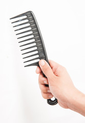 black comb in his hand on a white background