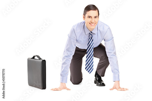 A smiling businessman with briefcase ready to run, looking at ca