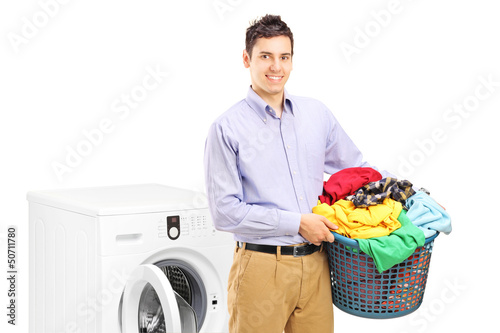 A smiling man with laundry bin posing next to a washing machine
