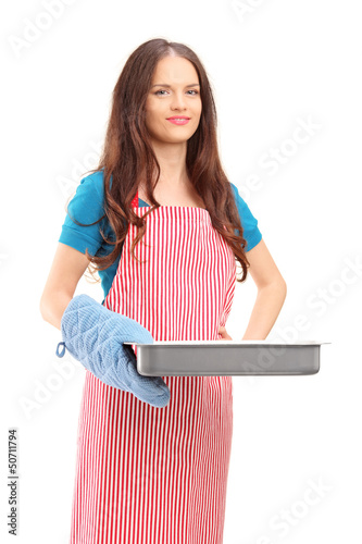 Beautiful woman with cooking mittens and apron holding a baking