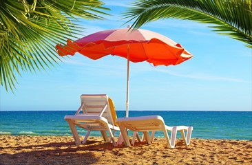 Beach chair and umbrella with palm trees on the beach