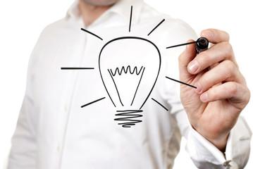 Businessman draws a light bulb, the symbol of the idea of