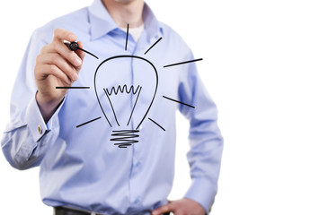 Businessman draws a light bulb, the symbol of the idea of