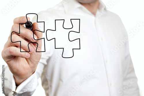 Businessman draws a puzzle at the presentation