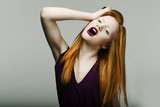 Shock. Unhappy Red Head Woman Pulling Her Hair in Frustration