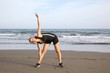 Healthy woman stretching on the beach