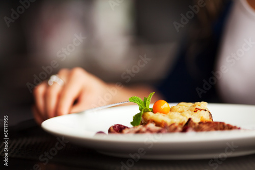 Female hand with a dinner at restaurant