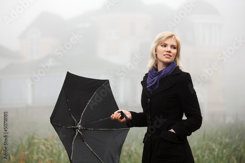 Young woman in autumn foggy morning