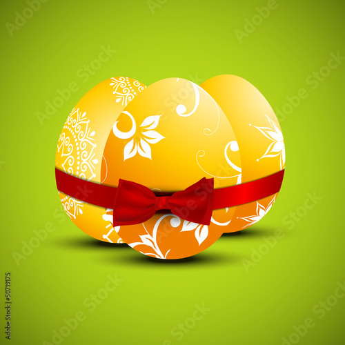 Floral decorated Easter Eggs wrapped with red ribbon on green ba