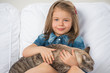 Cute little girl hugging tabby cat with love, looking at camera.