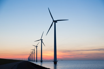 Long row of windturbines with sunset over the sea