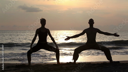 Couple doing exercise yoga on beach while sunset