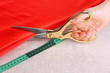 Seamstress cut red fabric on beige fabric background