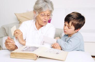 Enkel und Oma schauen ein Fotoalbum an