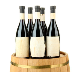 Wine bottles on wooden barrel, isolated on white