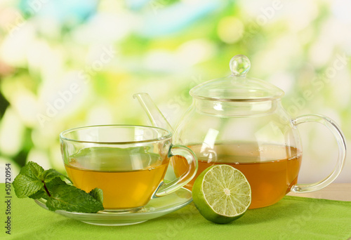 Cup of tea with mint and lime on table on bright background