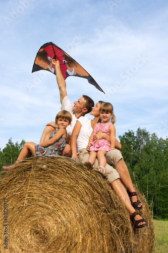 The happy family astride hay flying kite.
