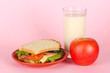 Sandwich on plate with apple and milk on pink background