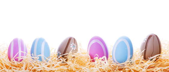 Colorful Easter eggs in the nest over white background