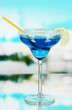 Blue cocktail in glass on blue natural background