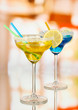 Yellow and blue cocktails in glasses on room background