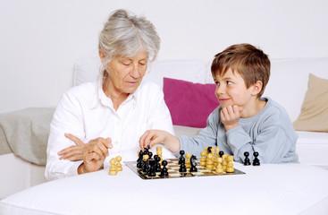 Oma und Enkel spielen Schach