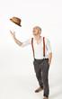 man throws his hat in air, portrait in studio