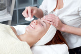young woman having facial beauty treatment at beauty salon