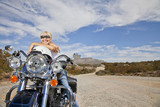 Senior woman in sunglasses poses on motorcycle on desert road