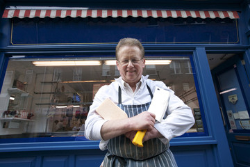 Portrait of a happy senior butcher standing with crossed cleavers in hands outside shop