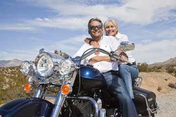 Senior couple on desert road sitting on motorcycle looking at camera